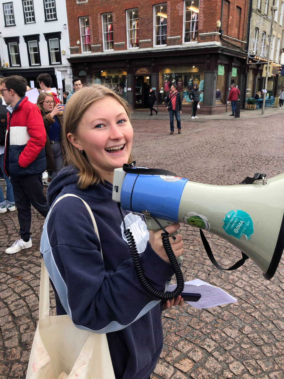 Photo of Esme Cavendish holding a megaphone, smiling. The new Access, Education and Participation Officer for undergraduate students